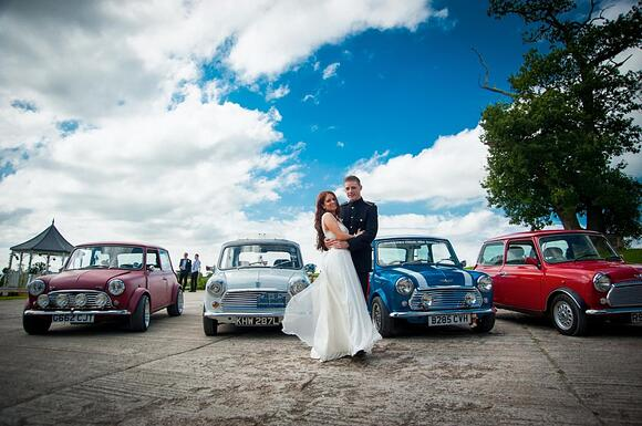 Bride and groom with classic mini car